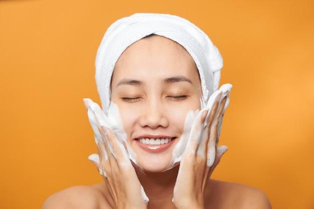 Heureuse jeune femme asiatique appliquant une crème pour le visage tout en portant une serviette et en touchant son visage. isolé sur fond orange