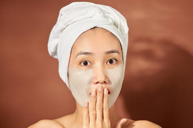 Heureuse jeune femme asiatique appliquant un masque d'argile sur son visage sur fond orange. fermer.
