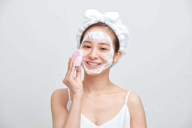 Heureuse jeune femme asiatique appliquant un nettoyant moussant sur son visage et portant une serviette sur la tête.