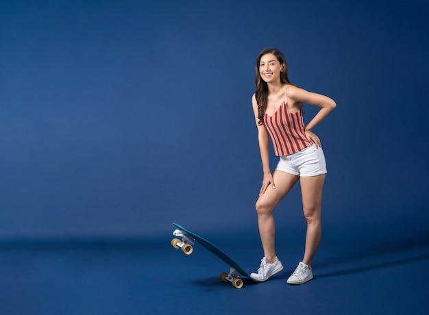 Heureuse jeune femme asiatique debout sur un surfskate ou une planche à roulettes sur la couleur bleue