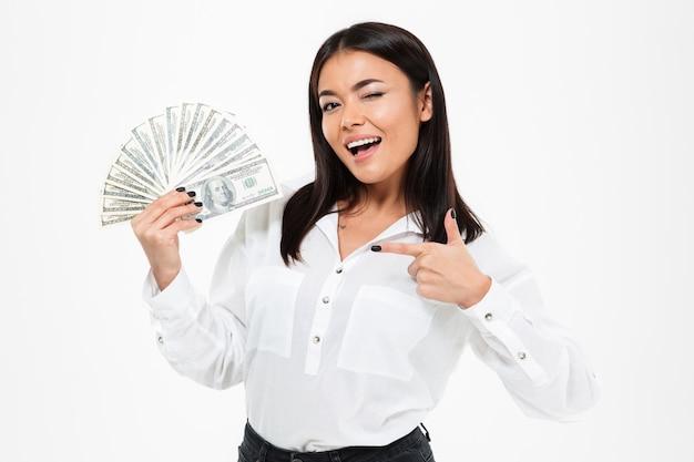 Heureuse jeune femme asiatique détenant de l'argent pointant.