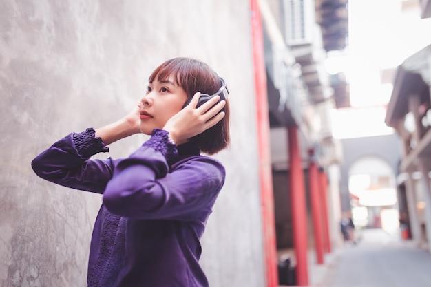 Heureuse jeune femme asiatique écoutant de la musique avec des écouteurs dans la rue.