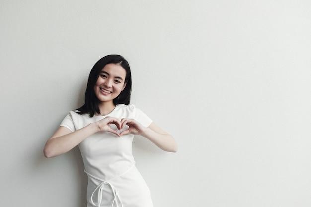 Heureuse jeune femme asiatique faisant ses mains en forme de coeur