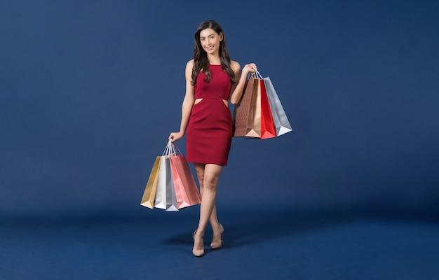 Heureuse jeune femme asiatique portant une robe rouge portant des sacs à provisions multicolores