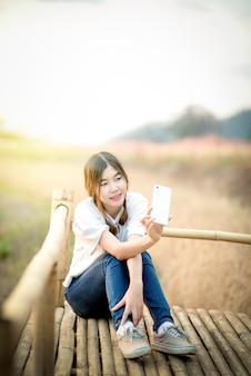 Heureuse jeune femme asiatique prenant selfie forme smartphone pendant l'été