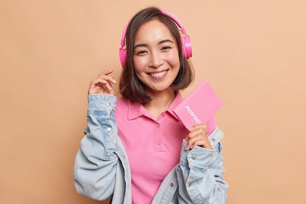 Heureuse jeune femme asiatique titulaire d'un passeport part en vacances après le verrouillage se réjouit des vols bon marché apprécie la musique populaire dans des écouteurs sans fil porte des vêtements à la mode recommande une bonne agence de voyage
