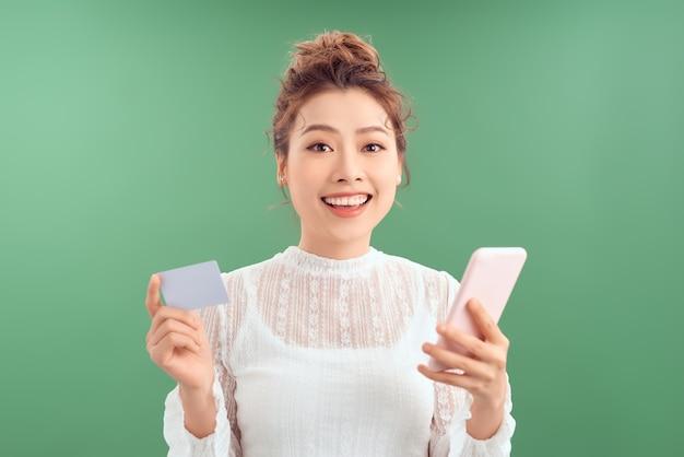 Heureuse jeune femme asiatique utilisant sa carte de crédit pour faire des achats en ligne avec son smartphone.