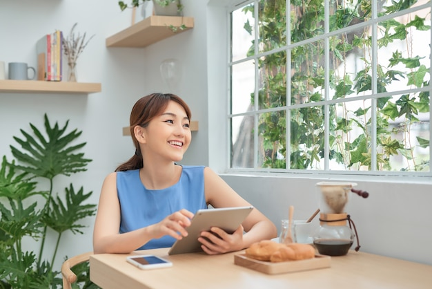 Heureuse jeune femme asiatique utilisant une tablette et buvant du café le matin
