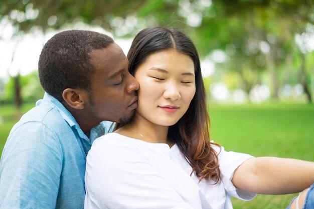 Heureuse jeune femme asiatique avec des yeux fermés, se sentir le baiser du petit ami africain en plein air