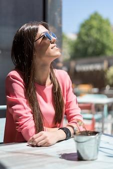 Heureuse jeune femme assise dans une terrasse de restaurant avec des lunettes de soleil