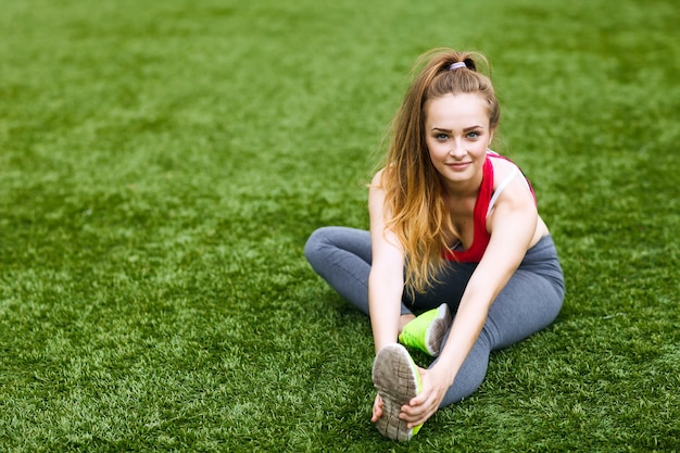 Heureuse jeune femme assise à l'extérieur en position de yoga