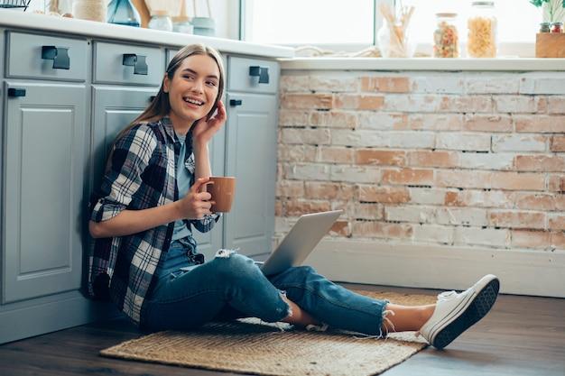 Heureuse jeune femme assise sur le sol avec du thé et un ordinateur portable
