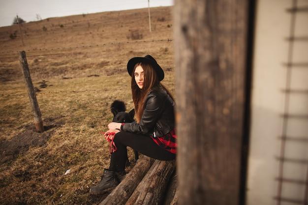 Heureuse jeune femme assise avec son chien noir