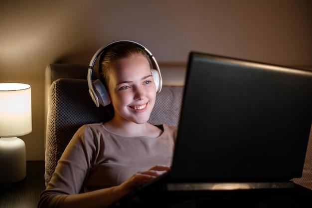 Heureuse jeune femme au casque travaillant ou étudiant la nuit sur un canapé à l'aide d'un ordinateur portable. adolescente au repos studing regarder un film sur un ordinateur portable. la navigation sur internet