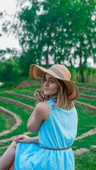 Heureuse jeune femme au chapeau de paille dans le jardin ensoleillé