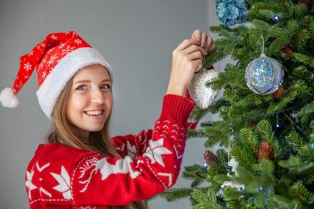 Heureuse jeune femme au chapeau de père noël décorant l'arbre de noël avec des boules