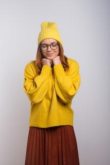 Heureuse jeune femme au chapeau tricoté et lunettes