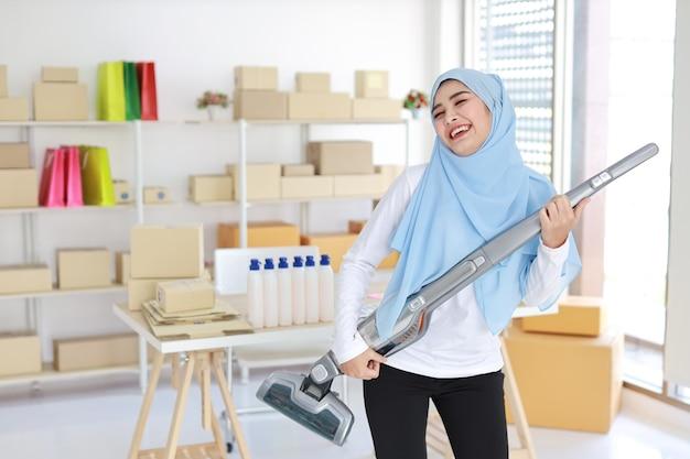 Heureuse jeune femme au foyer musulmane asiatique belle nettoyage et jouer à l'aspirateur comme la guitare