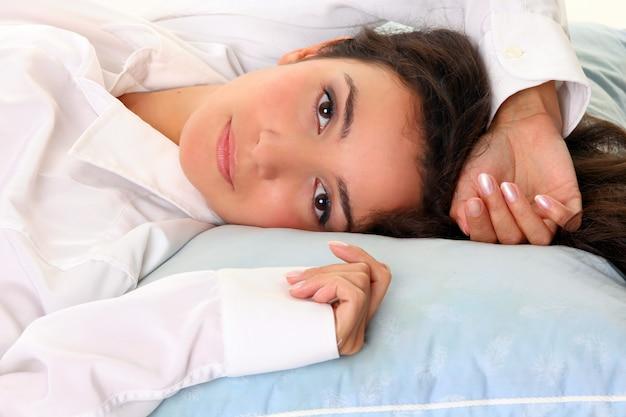 Heureuse jeune femme au lit