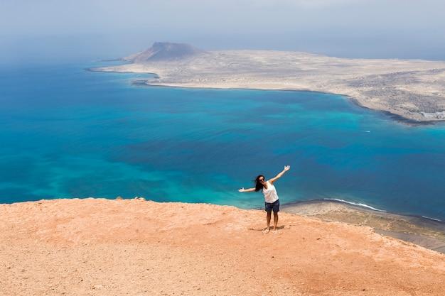 Heureuse jeune femme au sommet d'une montagne sur vue panoramique sur les îles canaries. ciel bleu clair et mer. vent. travel et style de vie
