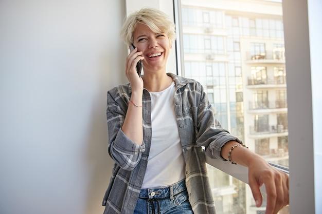 Heureuse jeune femme aux cheveux blonds courts dans des vêtements décontractés, parler au téléphone avec un ami, rire de blague, s'appuyer sur la fenêtre et regarder de côté
