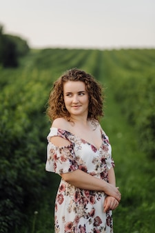 Heureuse jeune femme aux cheveux bouclés bruns, vêtue d'une robe, posant à l'extérieur dans un jardin