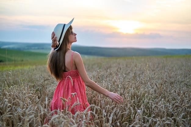 Heureuse jeune femme aux cheveux longs en chapeau de paille reposant sur un champ de blé doré au coucher du soleil.