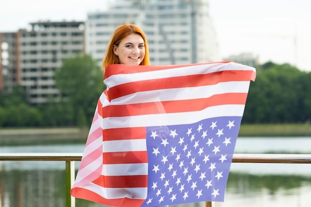 Heureuse jeune femme aux cheveux rouges avec le drapeau national des états-unis sur ses épaules