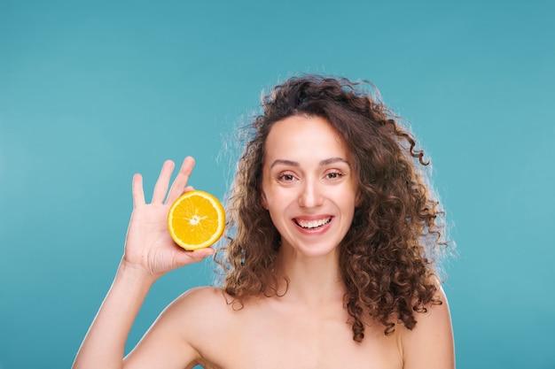 Heureuse jeune femme aux longs cheveux bouclés foncés tenant la moitié de l'orange juteuse fraîche dans la main droite tout en vous regardant avec un sourire sain