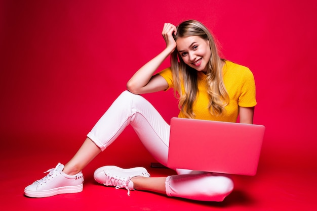 Heureuse jeune femme belle bouclée assise sur le sol avec les jambes croisées et utilisant un ordinateur portable sur le mur rouge.