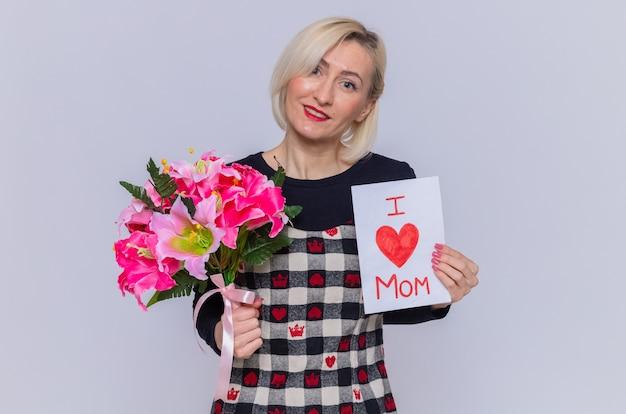Heureuse jeune femme en belle robe tenant une carte de voeux et un bouquet de fleurs à l'avant souriant célébrant la journée internationale de la femme debout sur un mur blanc