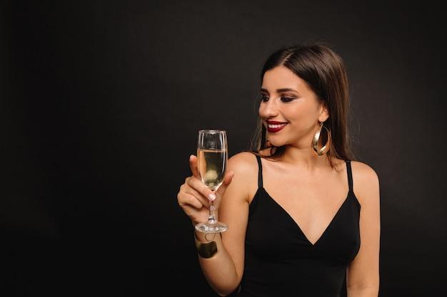Heureuse jeune femme avec des bijoux d'or en robe noire, boire du champagne