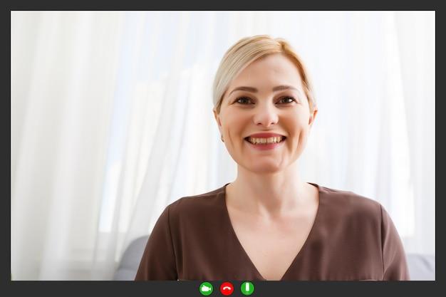 Heureuse jeune femme blogueuse enseignante candidate assise au bureau à domicile regarde la caméra en train de faire un entretien d'embauche en ligne lors d'une conférence de chat vidéo enregistrement vlog enseignement sur webinaire dans l'application, vue webcam