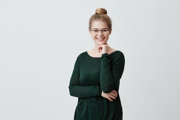 Heureuse jeune femme blonde ayant ses cheveux attachés en noeud portant de grandes lunettes et pull vert posant contre un mur gris tenant la main sous son menton ayant un large sourire
