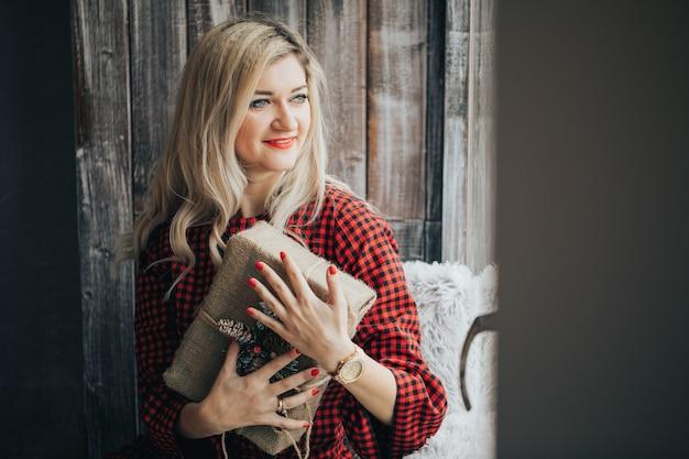 Heureuse jeune femme blonde dans un pull rouge a reçu un cadeau pour noël