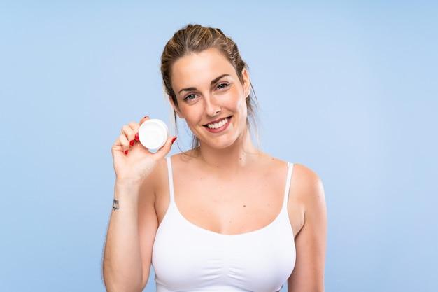 Heureuse jeune femme blonde avec un hydratant sur un mur bleu isolé