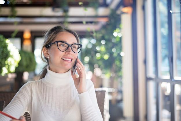 Heureuse jeune femme blonde à lunettes travaillant dans un restaurant