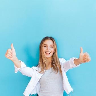Heureuse jeune femme blonde montrant le pouce en haut signe contre la toile de fond bleue