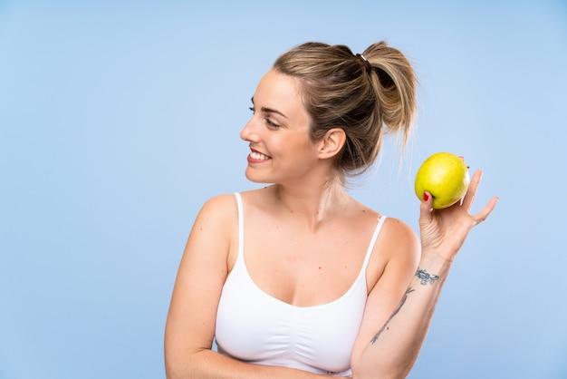 Heureuse jeune femme blonde avec une pomme