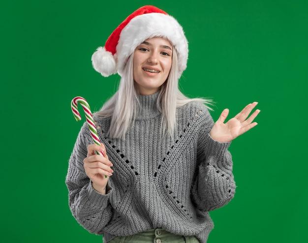 Heureuse jeune femme blonde en pull d'hiver et bonnet de noel tenant une canne en bonbon souriant joyeusement debout sur un mur vert