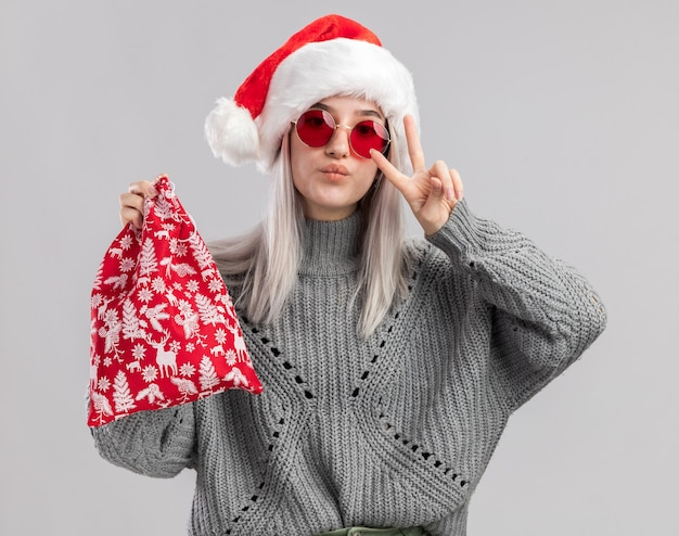 Heureuse jeune femme blonde en pull d'hiver et bonnet de noel tenant un sac rouge santa avec des cadeaux de noel montrant v-signe debout sur un mur blanc