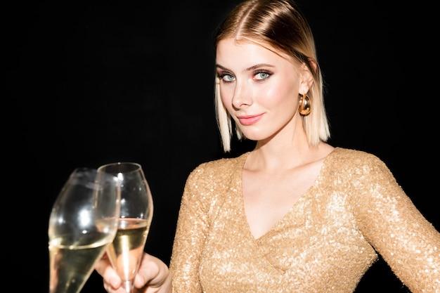 Heureuse jeune femme blonde en robe scintillante tinter la flûte de champagne avec quelqu'un et vous regarde tout en profitant de la fête