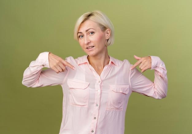 Heureuse jeune femme blonde slave se pointe du doigt