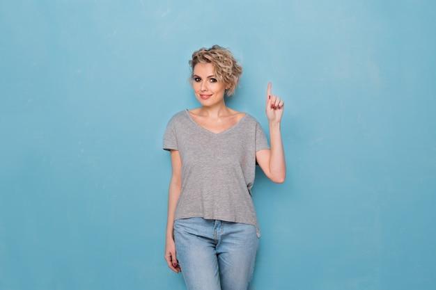 Heureuse jeune femme blonde surprise souriant largement à la caméra, pointant les doigts vers l'extérieur, montrant quelque chose d'intéressant et d'excitant sur fond bleu studio avec espace de copie pour votre texte