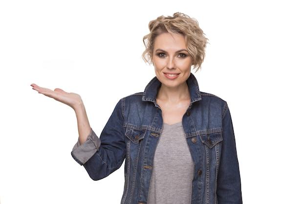 Heureuse jeune femme blonde surprise souriant largement à la caméra, pointant du doigt, montrant quelque chose d'intéressant et d'excitant sur fond de studio wight avec espace de copie pour votre