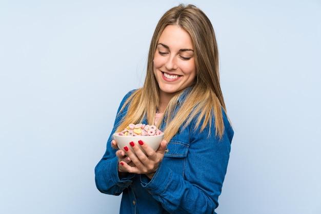 Heureuse jeune femme avec bol de céréales sur un mur bleu isolé