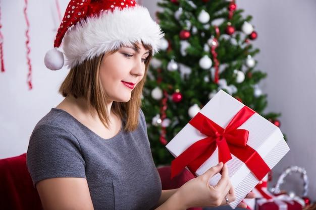 Heureuse jeune femme en bonnet de noel ouvrant une boîte-cadeau près d'un arbre de noël décoré