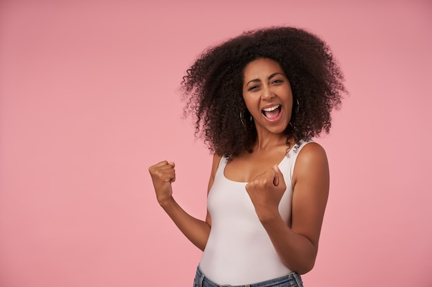 Heureuse jeune femme bouclée avec une coiffure décontractée avec un large sourire joyeux, célébrant la victoire de son équipe préférée, isolée sur rose avec les poings levés