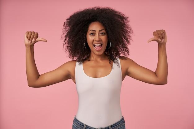 Heureuse jeune femme bouclée à la peau foncée portant une chemise blanche et un jean, levant les mains et se montrant avec les pouces, posant sur rose avec grande bouche ouverte
