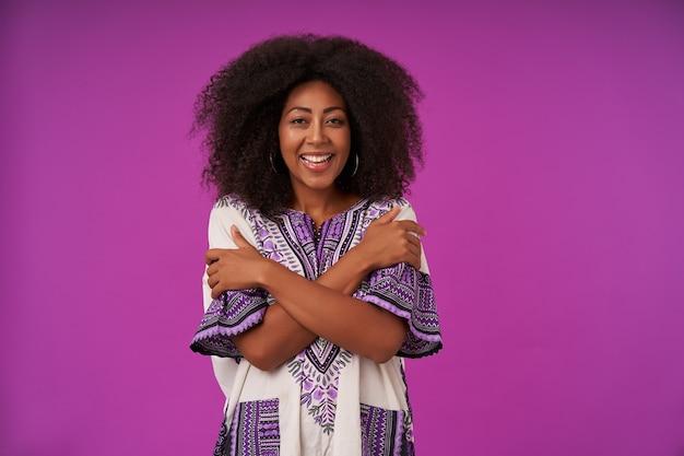Heureuse jeune femme bouclée avec une peau foncée portant une chemise à motifs blanche, posant sur violet avec les mains croisées sur sa poitrine joyeusement avec un large sourire